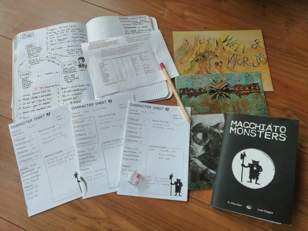 Some books, notes, character sheet, and the Macchiato Monsters rulebook